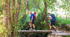 Hikers crossing foot bridge