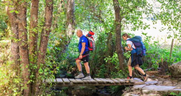 Hikers crossing foot bridge